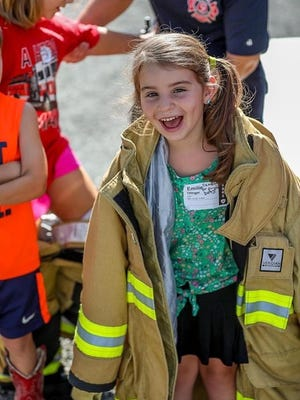 Emilie Olinger tries on a fire coat during the recent Detective Camp at Chili Crossroads Bible Church near Fresno.