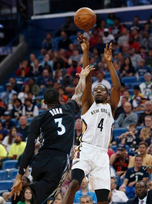 New Orleans Pelicans guard Jordan Crawford (4) shoots against Minnesota Timberwolves guard Kris Dunn (3) in the second half of an NBA basketball game in New Orleans, Sunday, March 19, 2017. (AP Photo/Gerald Herbert)