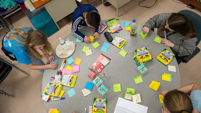 Students write positive affirmations on Post-it notes for their peers in Mrs. Kristy Bankert's class on Friday, March 31, 2017.  Every student will receive a message on his or her locker. The notes are to encourage the students to do their best on the upcoming PSSA tests.