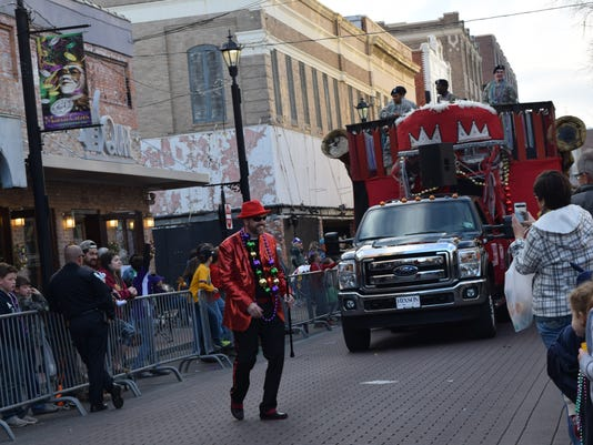 Members of the Krewe of Boogaloo float hand out throws as the float passes down Third Street in Alexandria Friday evening in the Hixson Classic Cars & Cheerleaders Parade.