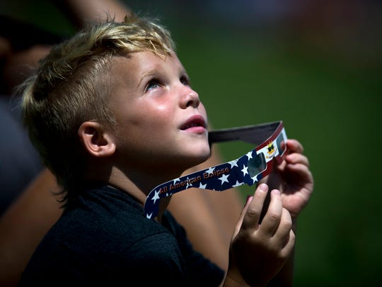 Ryker Wade watches the solar eclipse reach totality as he celebrates his seventh birthday at The Cove in Farragut on Monday, August 21, 2017.