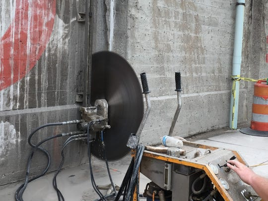 A worker for American Concrete Cutting Services operates a 54-inch circular saw on a 17- to 22-inch thick concrete wall outside Central Station.