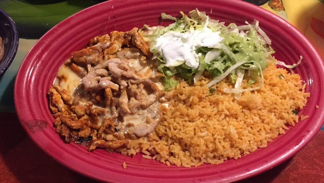 The arroz con pollo dinner includes Spanish rice and a salad.