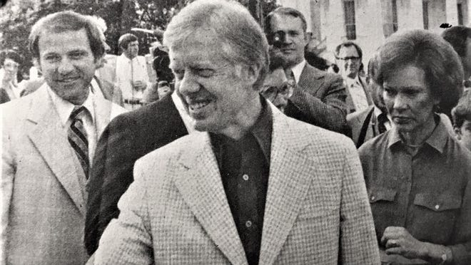 Larry Sconyers (left) looks on as President Carter and his wife greet barbecue staff at White House.