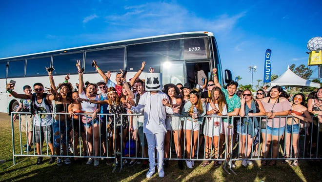 EDM artist Marshmello, who never removes his head mask, gave away VIP passes to shuttle bus users at Coachella on Sunday.