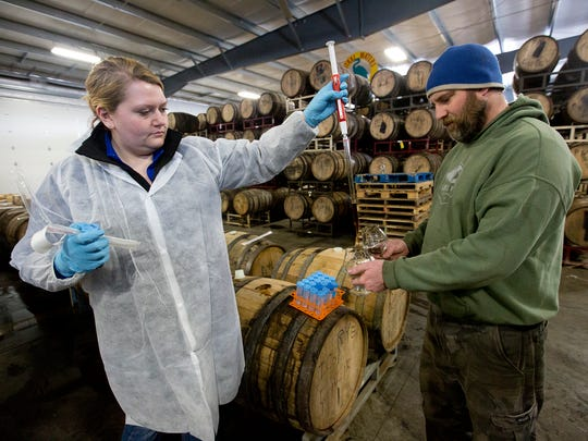 Lab technician Haley Meyer, left, and equipment manager Shane Passwaters test an imperial chocolate oatmeal porter aged in a rye barrel.