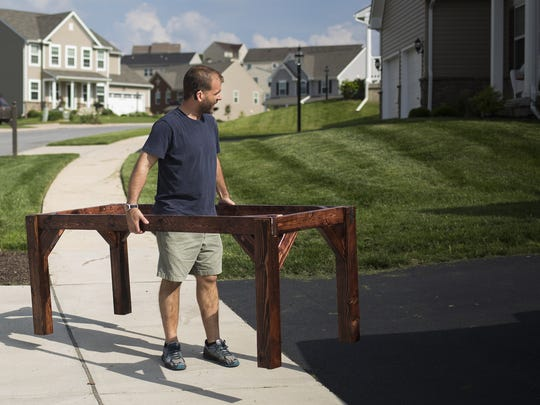 Neil Barnes carries a table while loading a trailer for an upcoming event. Neil and Missy Barnes make banquet tables in their garage in Seven Valleys that they rent for social events.
