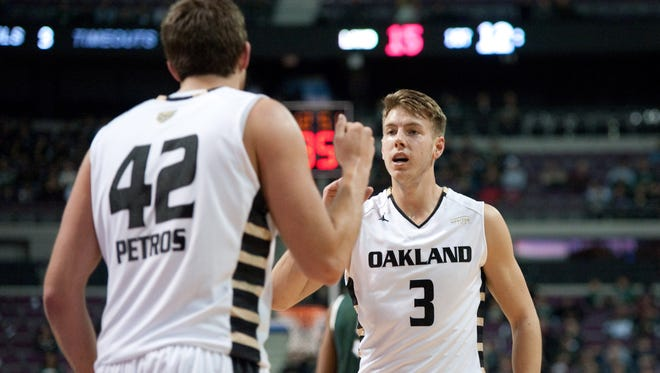 Oakland Golden Grizzlies guard Travis Bader (3) and center Corey Petros (42) celebrate during the first half against the Michigan State Spartans at The Palace of Auburn Hills.