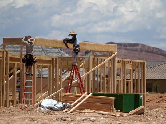 Workers frame a new house in the Little Valley area