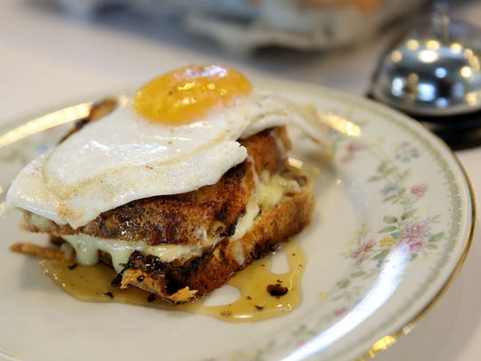 A fried duck egg crowns raclette grilled cheese on cranberry walnut bread, all drizzled with black truffle honey at Milktooth, 534 Virginia Ave.