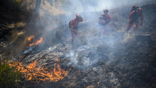 An inmate hand crew works the fire line to fight a wildfire in Sonoma County near Geyserville in October 2019. California is scrambling to find sufficient wildland firefighters amid a coronavirus outbreak that has depleted the ranks of inmates who usually handle some of the toughest duties.
