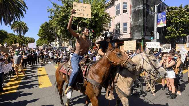 Chinedu Anigbogu rides a horse as demonstrators rally in San Francisco's Mission District June 3 to protest the death of George Floyd.