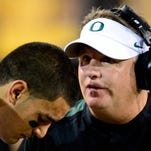 Former Oregon head coach Chip Kelly talks with quarterback Marcus Mariota on the sideline during a game in 2012.