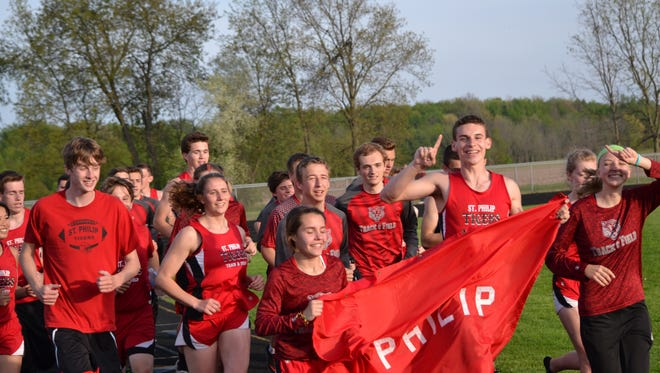 Members of the St. Philip boys and girls track and field teams celebrate their SCAA West Division titles on Wednesday.