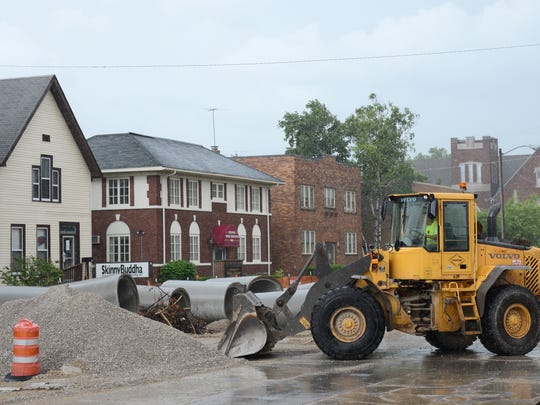 A contractor moves gravel as construction continues Tuesday on Monroe Avenue in Green Bay.