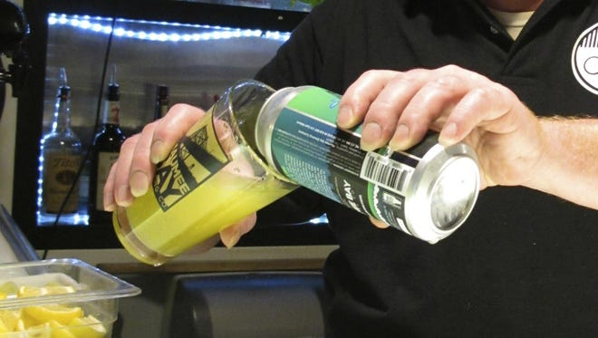 """Bartender Rodney Shipp pours a can of """"Alegae Bloom"""" beer at Maumee Bay Brewing Co. in Toledo, Ohio."""