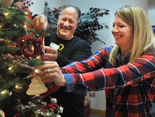 John Buckley, president and CEO of Texoma Community Credit Union, and Adult Protective Service supervisor Crystal Sullivan decorate this year's Tree of Life in the lobby of the credit union's Sheppard Access Road location Friday morning.