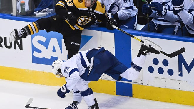 Boston Bruins center Karson Kuhlman (83) hits Tampa Bay Lightning center Anthony Cirelli (71) during the third period of an NHL hockey playoff game  Wednesday, Aug. 5, 2020 in Toronto.