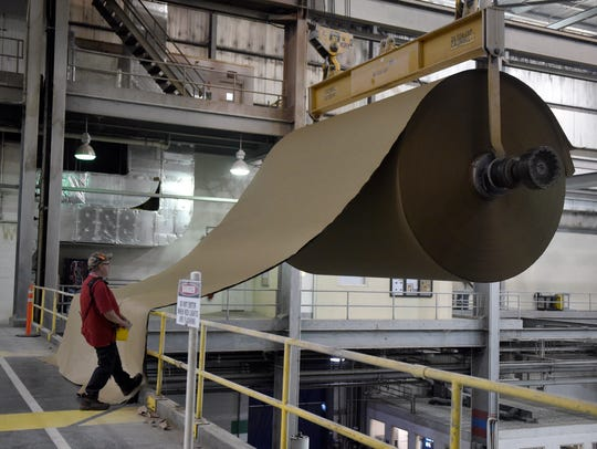 Mike Gower a dry end team member at International Paper uses a lift to transport a new roll of paper while working at the plant in Henderson, Kentucky in 2016.
