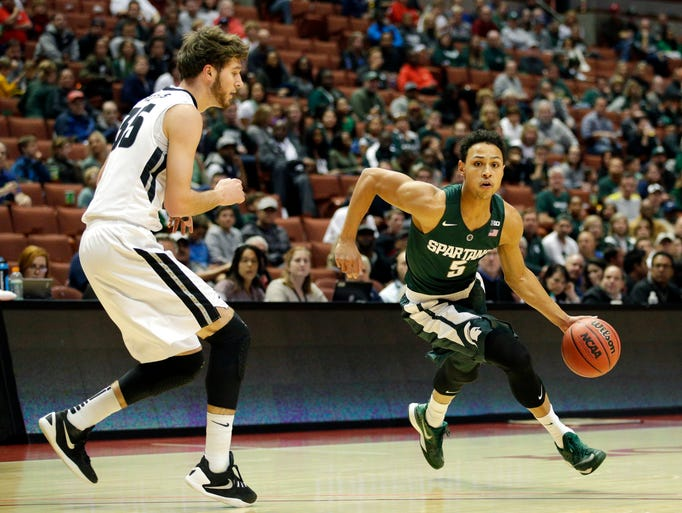 Michigan State guard Bryn Forbes, right, dribbles as