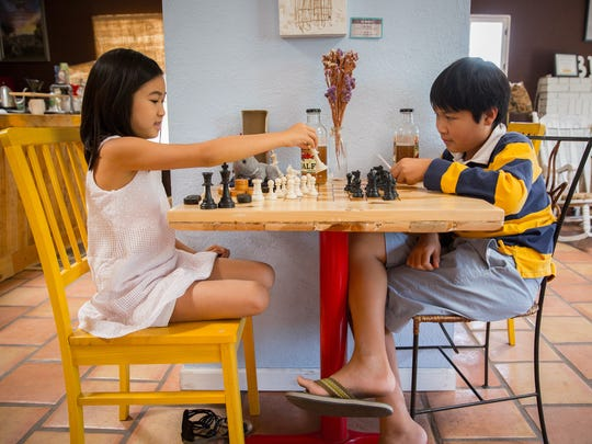 Marteena Matmanivong, 8, plays chess with 12-year-old brother Matthew Matmanivong at Beck's Coffee House on Mesquite Street.