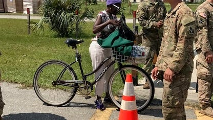 Johnnie Smith of Dunbar loads up her bicycle at a distribution point for food and water at Fleamasters Fleamarket on Dr. Martin Luther King Jr. Boulevard.