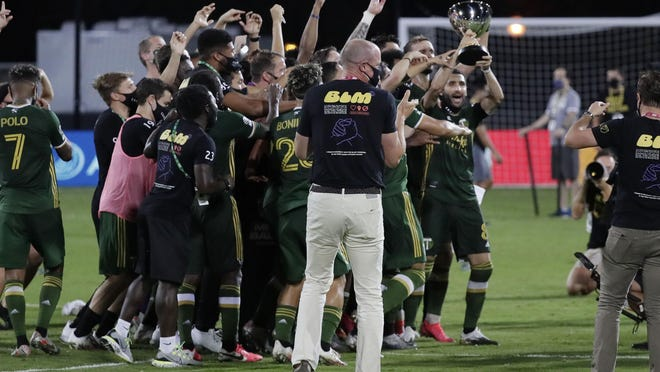 Portland Timbers players celebrate after defeating Orlando City 2-1, Tuesday, night in Kissimmee, Fla.