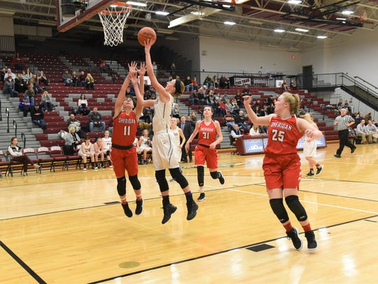 John Glenn's Madison Hunter takes a shot over Sheridan's Jena Wharton earlier this season. Hunter was one of three area girls to make first team in Division II.