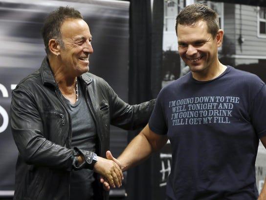 Bruce Springsteen, left, greets a fan wearing a shirt