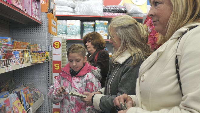 At the 2013 ePIFanyNow event, Peyton Broadway, 9, from left, Lil Waar, Patti Leppanen-DeNike and Kim Wiseman, get some dollar bills ready along with a pay it forward card to place in various areas of a local store.