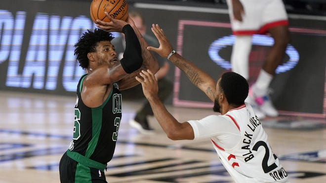 The Celtics' Marcus Smart takes a shot over the Raptors' Norman Powell in the second half of Tuesday night's Eastern Conference semifinal. Smart hit five straight 3-pointers in just 3:04 at the start of the fourth quarter to spark Boston.