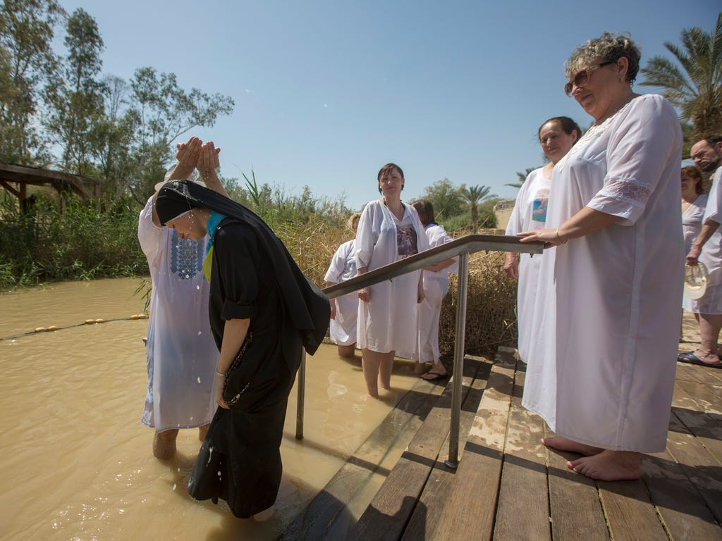 Christian pilgrims perform baptisms at the Qasr al Yahud site on the Jordan River, near the West Bank city of Jericho.The site is believed to be the place where Jesus was baptized by John the Baptist.