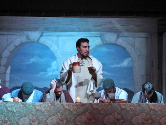 Gabriel Varela, playing Jesus, offers bread and wine to his disciples during an April 1, 2015, Passion Play performance at the McGee Park Convention Center in Farmington.