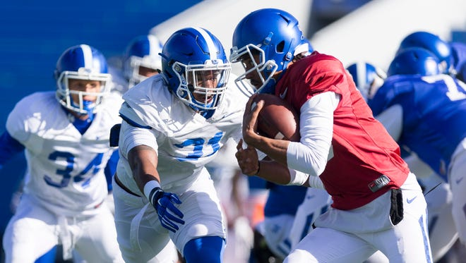 Kentucky Wildcats linebacker Jamar Watson tackles quarterback Stephen Johnson during the Kentucky football open practice session.
