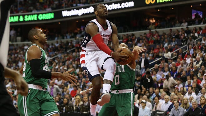 Washington Wizards guard John Wall (2) shoots the ball as Boston Celtics guard Avery Bradley (0) and Celtics center Al Horford (42) defend in the third quarter in game three of the second round of the 2017 NBA Playoffs at Verizon Center.