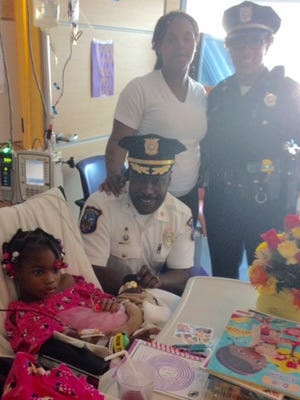 Wilmington Police Chief  Bobby Cummings (center) and Cpl. Diana Brown (right) on Thursday visit with 6-year-old shooting victim Armonie Fields and her mother, Aerion Fields, at Nemours/Alfred I. duPont Hospital for Children in Rockland.