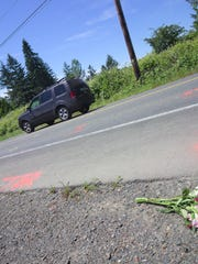 Flowers lay along Finch Road on Bainbridge Island near where two joggers were hit by a vehicle on June 17, 2018.