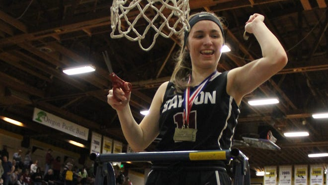 Dayton senior Shawnie Spink smiles after cutting down a piece of the net on Saturday, March 3, 2018.
