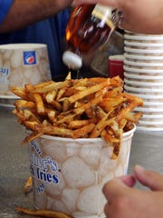 A hungry customer dumps vinegar onto a bucket of Thrashers French Fries.