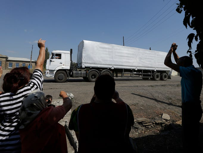 People cheer as they greet the first Russian truck carrying relief supplies as it passes the border post on Aug. 22 in Izvaryne, eastern Ukraine. The first trucks in a Russian aid convoy crossed into eastern Ukraine without approval from the government in Kiev after more than a week's delay.