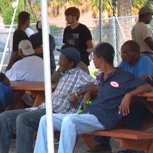Jacksonville residents sit outside at Jacksonville Day Resource Center and keep shaded from the sun