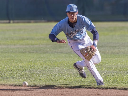Redwood's Hunter Bryan fields a batted ball from Hanford