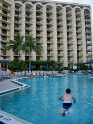 In this file photo, guests splash and relax poolside