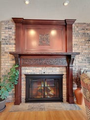 A grand hand-carved gas fireplace adorns the living