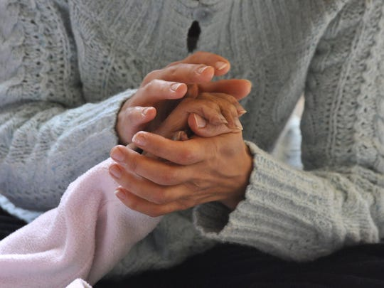 Laura Bailey holds her mother's hand. A home funeral