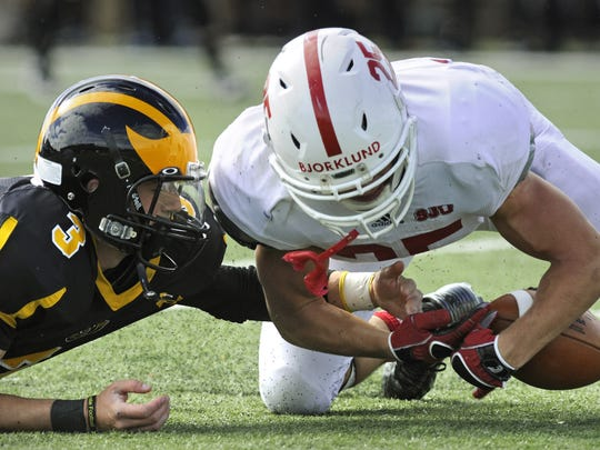 Gustavus quarterback Mitch Hendricks (left) and Reid Bjorklund of St. John's go for a loose football in last year's matchup between the two teams in St. Peter.