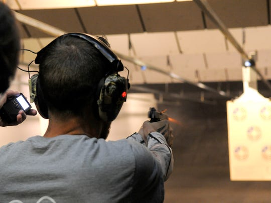 Shane Johnson of Cold Spring fires a practice round on Tuesday morning at the Firing Line indoor range in Sauk Rapids. He later shot a pistol and a rifle in an American Marksman competition. Qualifying scores are visible on online leaderboards. The Firing Line is among the participating ranges in the U.S.