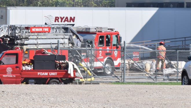 A Newark firefighter wets down bales of insulation outside an Owen Cornings' warehouse Tuesday afternoon. No one was hurt in the reported fire.