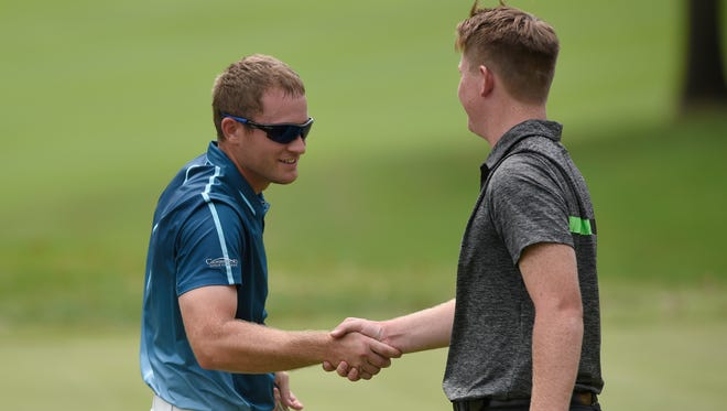 Logan Osborne (left) shakes hands with Stewie Hobgood on the 18th green after Osborne won the Evansville Courier & Press City tournament at 4-under par at Evansville Country Club in Evansville Sunday. Hobgood finished second at even par.