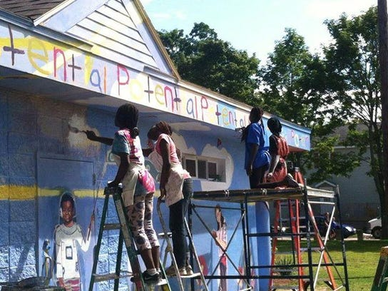 Youths work on a mural at a building near the Boys